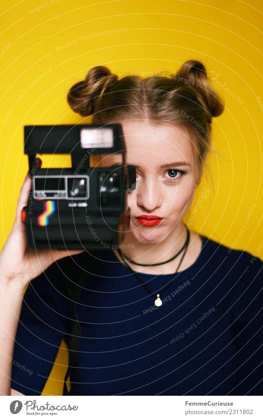 Young woman with an instant camera Frau Mensch Jugendliche Junge Frau schön rot 18-30 Jahre Erwachsene Lifestyle gelb feminin Stil modern blond Kreativität