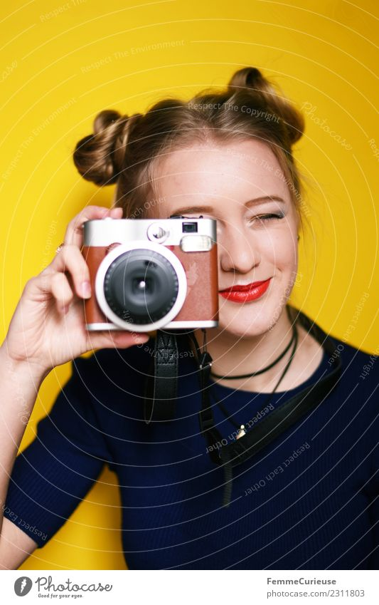 Young woman taking pictures with an instant camera Frau Mensch Jugendliche Junge Frau rot 18-30 Jahre Erwachsene gelb feminin retro Technik & Technologie