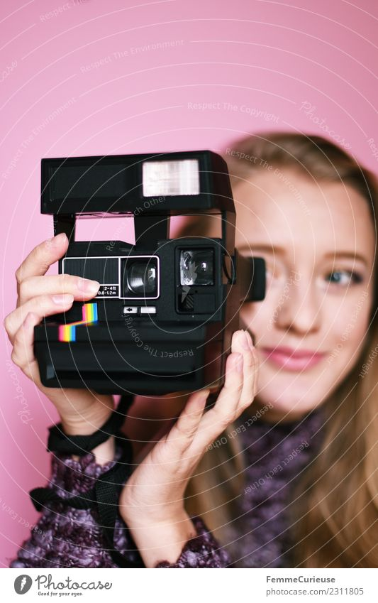 Young blonde girl using an instant camera Frau Mensch Jugendliche Junge Frau Hand Freude 18-30 Jahre Erwachsene Lifestyle feminin rosa Freizeit & Hobby
