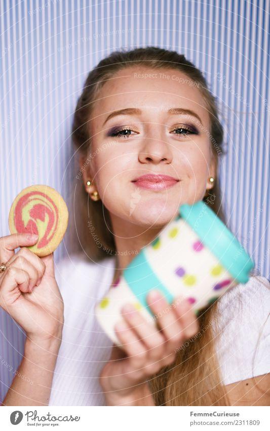 Young blonde girl holding a coffee mug & cookie Frau Mensch Jugendliche Junge Frau Freude 18-30 Jahre Erwachsene feminin Freizeit & Hobby Lächeln genießen