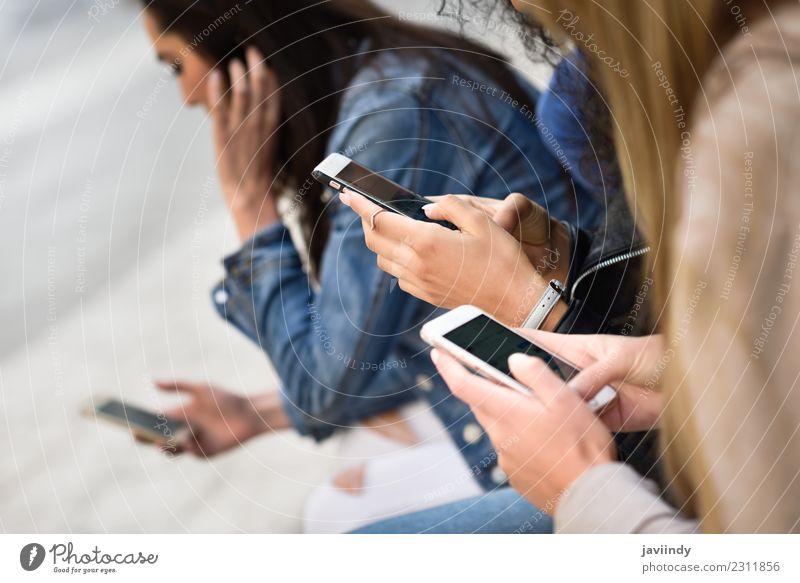 Hände von jungen, nicht erkennbaren Menschen, die Smartphones im Freien im städtischen Hintergrund benutzen. Lifestyle Telefon Computer Technik & Technologie