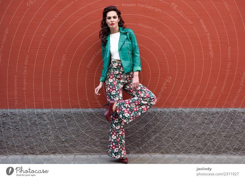 Junge brünette Frau, Modell der Mode, trägt grüne moderne Jacke und Blume Hose auf rote Wand Lifestyle Stil schön Haare & Frisuren Gesicht Mensch feminin