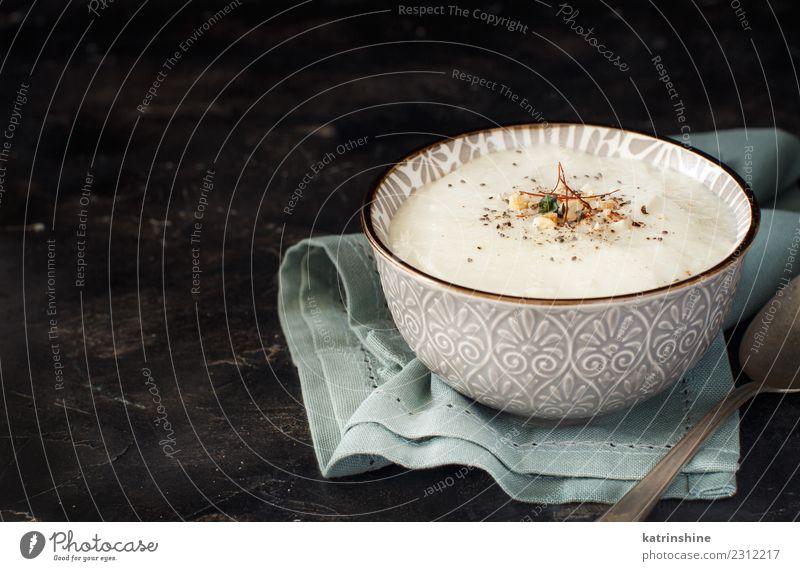 Cremefarbene Blumenkohlsuppe in einer Schüssel auf dunklem Hintergrund Gemüse Suppe Eintopf Kräuter & Gewürze Mittagessen Abendessen Vegetarische Ernährung Diät