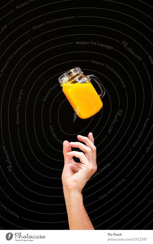 EINE HAND GREIFT VON UNTEN NACH EINEM GLAS MIT GELBEN FLUID Lebensmittel Frucht Orange Frühstück Bioprodukte Vegetarische Ernährung Diät Fasten Getränk Limonade