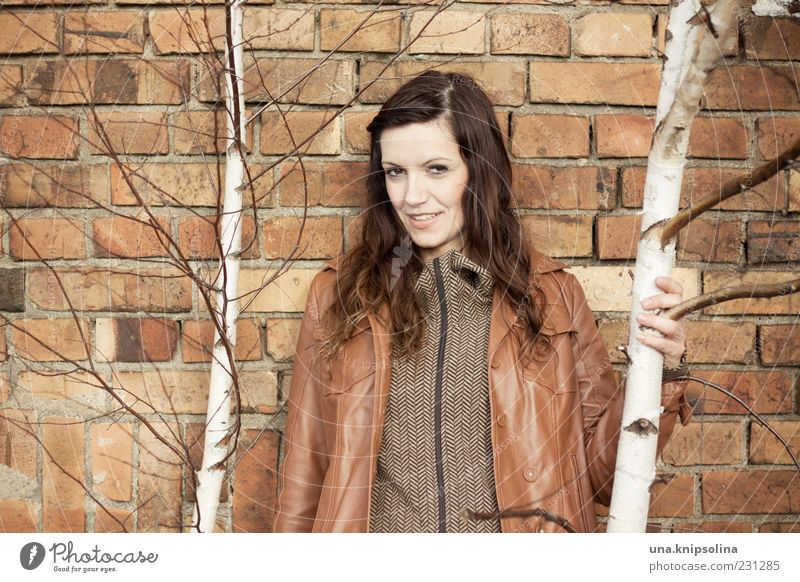 wall feminin Junge Frau Jugendliche Erwachsene 1 Mensch 18-30 Jahre Baum Birke Mauer Wand Jacke Leder brünett langhaarig berühren festhalten Lächeln