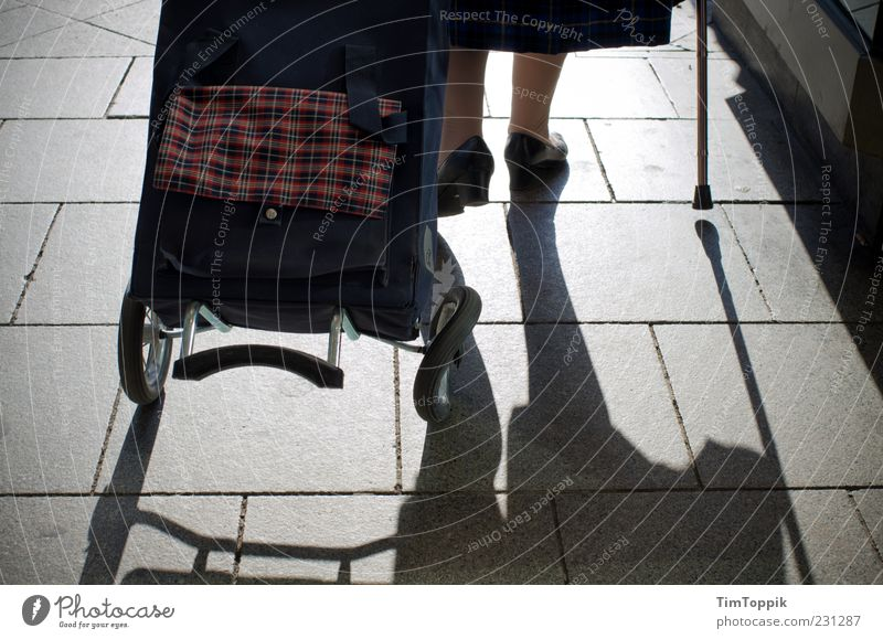 Es läuft nicht mehr rund... Beine Fuß 1 Mensch 60 und älter Senior gehen Armut Armutsgrenze Einkaufstasche alt Stock Gehhilfe Spazierstock Schatten kaputt Rad