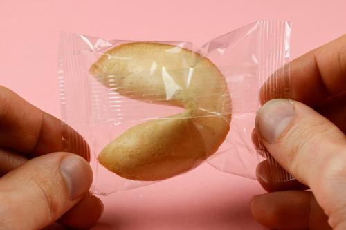 Glückskeks verpackt Süßwaren Mann Erwachsene Finger 30-45 Jahre wählen festhalten rosa Schutz Zukunftsangst entdecken Hoffnung Keks Verpackungsmaterial