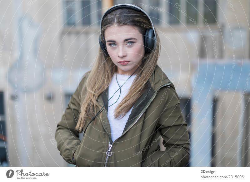 Junges Mädchen mit Kopfhörern auf der Straße stehend Lifestyle Freude Glück schön Leben Erholung Freizeit & Hobby Musik Technik & Technologie Mensch Frau