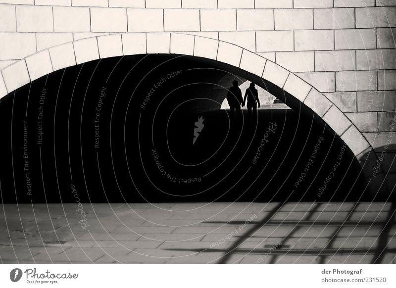 hand in hand Spaziergang Mensch maskulin Frau Erwachsene Mann Paar Partner 2 Brücke Tunnel Mauer Wand Wege & Pfade Stein gehen zusammengehörig Schwarzweißfoto