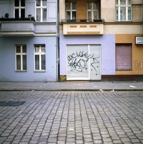 Berlin XII Neukölln Stadt Hauptstadt Menschenleer Haus Verkehrswege Straße Stein Graffiti Häusliches Leben blau rot Pflastersteine Rollladen Ladengeschäft