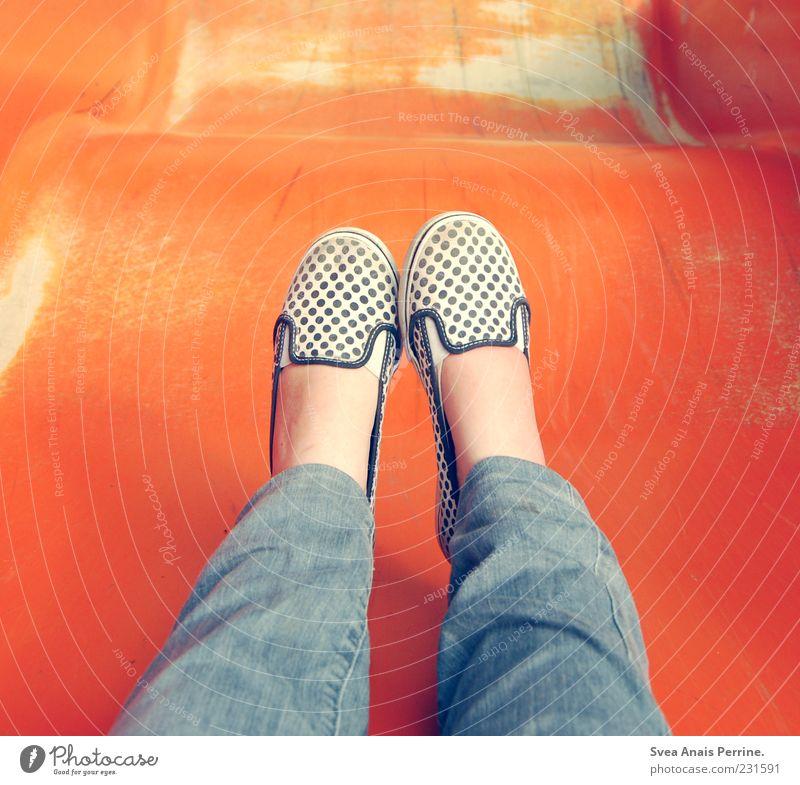 rutsche. Mensch Jugendliche feminin Spielen Beine Fuß Schuhe sitzen Beginn Kindheitserinnerung Jeanshose Junge Frau Lebensfreude Spielplatz Rutsche gepunktet