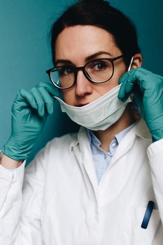 Female doctor putting on her face mask Arbeit & Erwerbstätigkeit Beruf Arzt kompetent anziehen Vorbereitung Brille brünett Kittel Handschuhe türkis