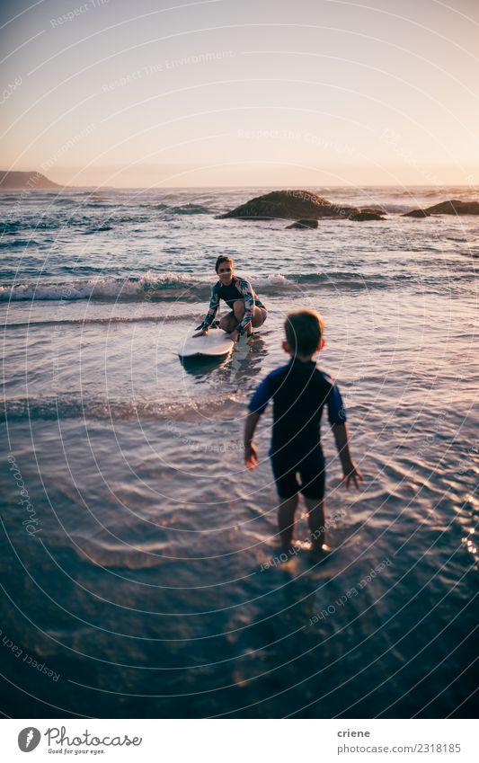 Mutter unterrichtet ihren Sohn beim Surfen mit dem Surfbrett. Lifestyle Freude Glück Erholung Freizeit & Hobby Ferien & Urlaub & Reisen Sommer Strand Meer Sport