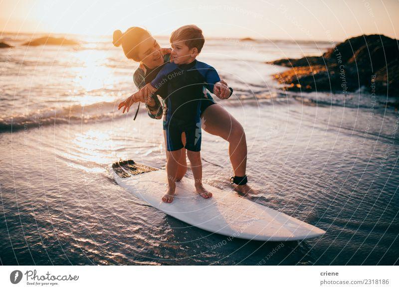 Kleiner Junge und Mutter üben das Surfen am Strand. Lifestyle Freude Glück Erholung Freizeit & Hobby Ferien & Urlaub & Reisen Sommer Meer Sport Kind Schule