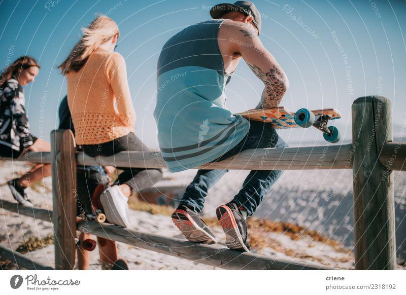 Gruppe von Freunden, die mit Skateboards am Strand herumhängen. Freude Leben Freizeit & Hobby Sommer Mensch Frau Erwachsene Mann Freundschaft Menschengruppe