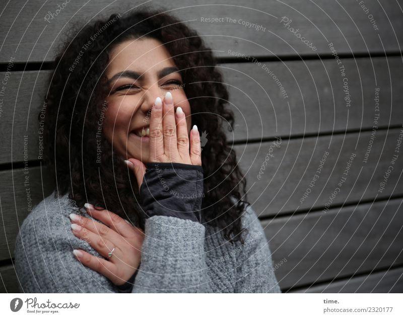 Nikolija feminin Frau Erwachsene 1 Mensch Mauer Wand Pullover brünett langhaarig Locken Holz festhalten lachen Freundlichkeit Fröhlichkeit Glück Stimmung Freude