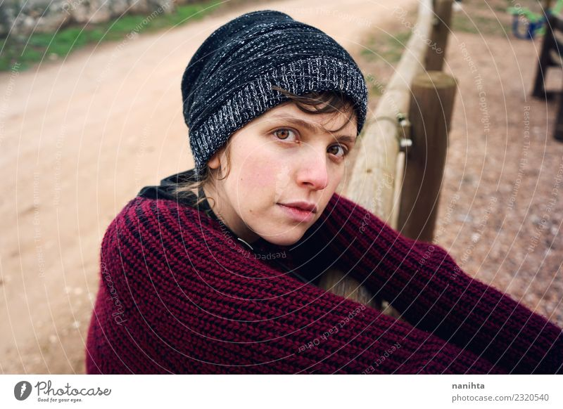 Junge traurige Frau Otudoors Lifestyle Stil Mensch feminin Junge Frau Jugendliche 1 18-30 Jahre Erwachsene Natur Park Pullover Hut brünett Holz warten