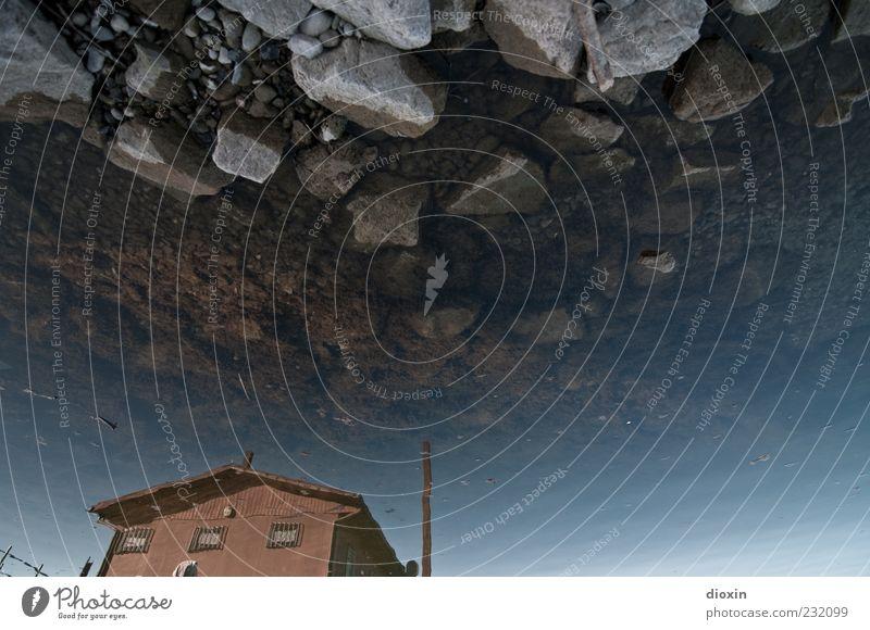 stony skies over paradise pt.1 blau Wasser Haus kalt Stein braun Felsen nass Hafen Seeufer Flüssigkeit Hütte trashig bizarr Surrealismus Wasseroberfläche
