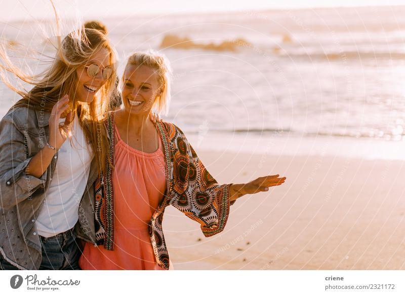 Zwei junge erwachsene Freundinnen, die am Strand plaudern und lachen. Lifestyle Freude Glück schön Ferien & Urlaub & Reisen Sommer Sonne Wellen Frau Erwachsene