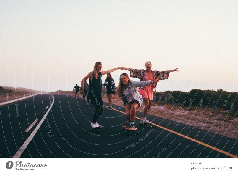 Junge erwachsene Gruppe von Freunden, die zusammen Longboards auf der Straße fahren. Lifestyle Freude Glück Freizeit & Hobby Abenteuer Freiheit Sport