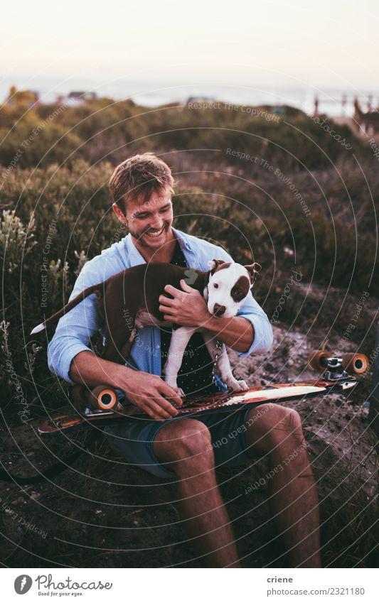 Lächelnder junger Erwachsener mit süßem Welpen auf Skateboard Freude Glück Spielen Sommer Frau Familie & Verwandtschaft Freundschaft Tier Haustier Hund Liebe