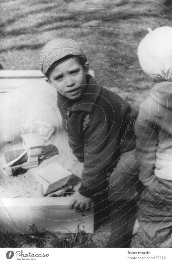 kleiner mann im sandkasten Kind Spielen Sandkasten Geschwister Schwarzweißfoto Blick Schatten