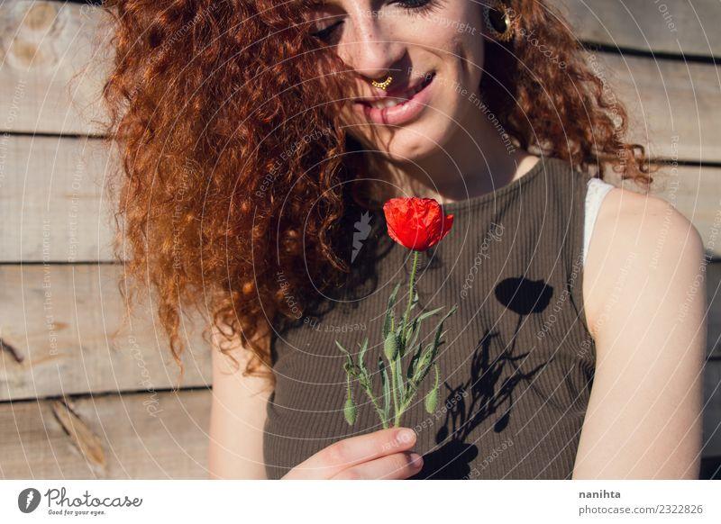 Junge Rothaarige hält eine Mohnblume in den Händen. Lifestyle Stil Freude schön Haare & Frisuren Haut Gesicht Wellness harmonisch Sinnesorgane Erholung Mensch