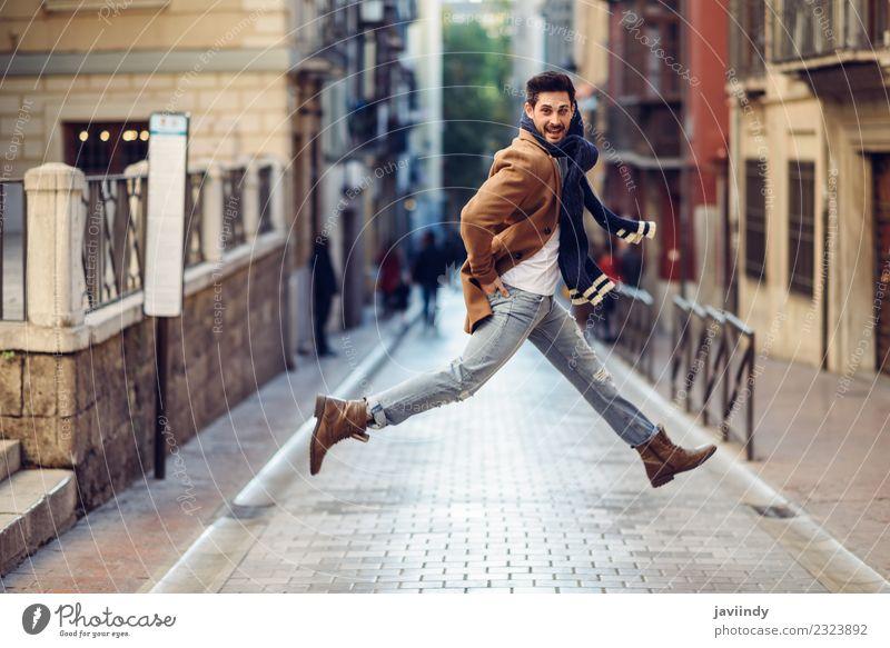 Glücklicher Mann beim Springen in Winterkleidung auf der Straße Stil Freude Mensch Junger Mann Jugendliche Erwachsene 1 18-30 Jahre Herbst Mode Bekleidung