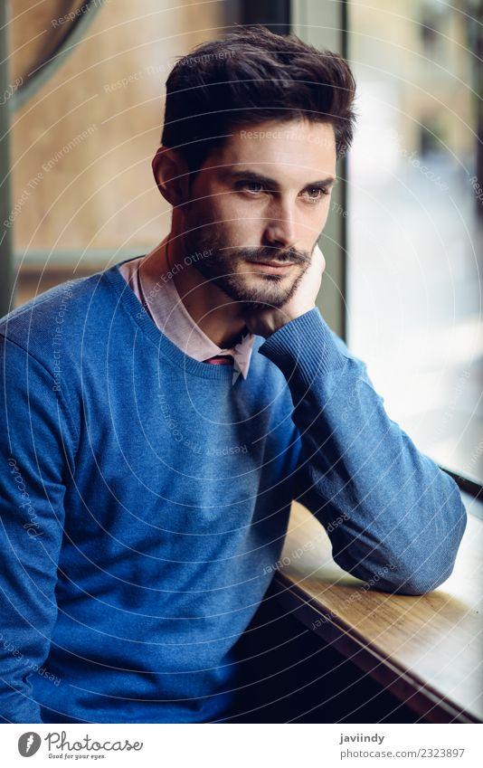 Nachdenklicher Mann mit verlorenem Blick in der Nähe eines Fensters in einem modernen Pub. Lifestyle Stil schön Haare & Frisuren Mensch maskulin Junger Mann