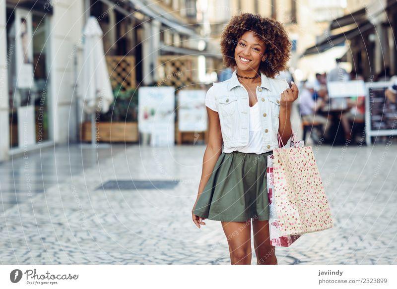 Junge schwarze Frau mit Einkaufstaschen auf der Straße. Lifestyle kaufen schön Haare & Frisuren Mensch feminin Junge Frau Jugendliche Erwachsene 1 18-30 Jahre