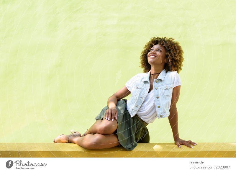 Junge schwarze Frau, Afrofrisur, sitzt lächelnd an einer Wand Lifestyle Stil Glück schön Haare & Frisuren Gesicht Mensch feminin Junge Frau Jugendliche