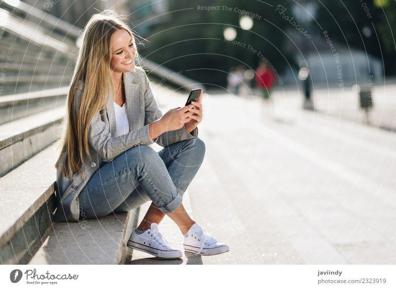 Frau, die auf ihr Smartphone schaut und im urbanen Hintergrund lächelt. Lifestyle Stil Glück schön Haare & Frisuren Telefon PDA Mensch feminin Junge Frau