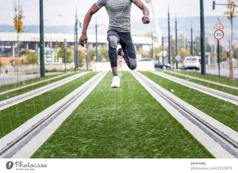 Ein schwarzer Mann, der im urbanen Hintergrund springt. Lifestyle Sport Joggen Mensch maskulin Junger Mann Jugendliche Erwachsene 1 18-30 Jahre Straße Fitness