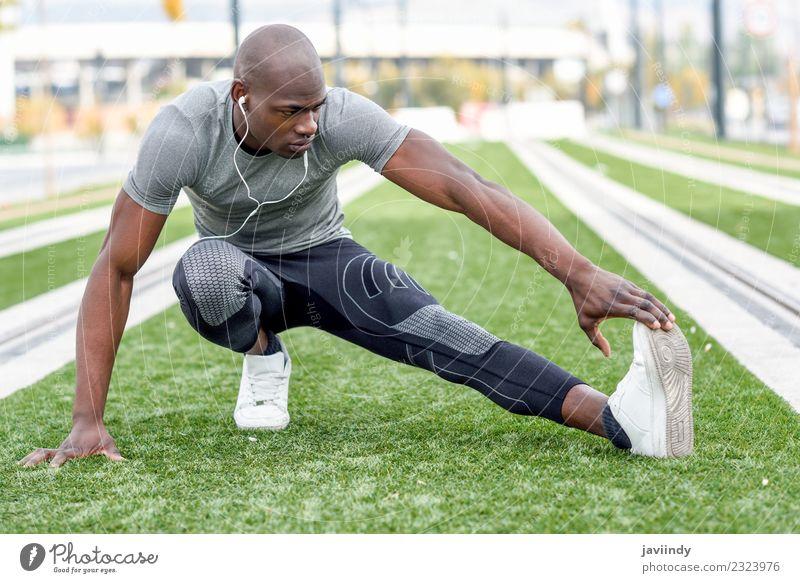 Schwarzer Mann, der sich dehnt, nachdem er im urbanen Hintergrund gelaufen ist. Lifestyle Körper Sport Joggen Mensch maskulin Junger Mann Jugendliche Erwachsene