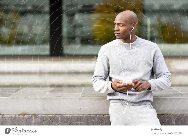 Attraktiver schwarzer Mann, der Musik mit Kopfhörern im Freien hört. Lifestyle Glück Sport Telefon PDA Technik & Technologie Mensch Junger Mann Jugendliche