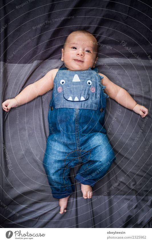 süßes Baby, das in einer Perle liegt und Jeans-Latzhose trägt. Glück schön Gesicht Bad Kind Mensch Kleinkind Junge Frau Erwachsene Kindheit Spielzeug Lächeln
