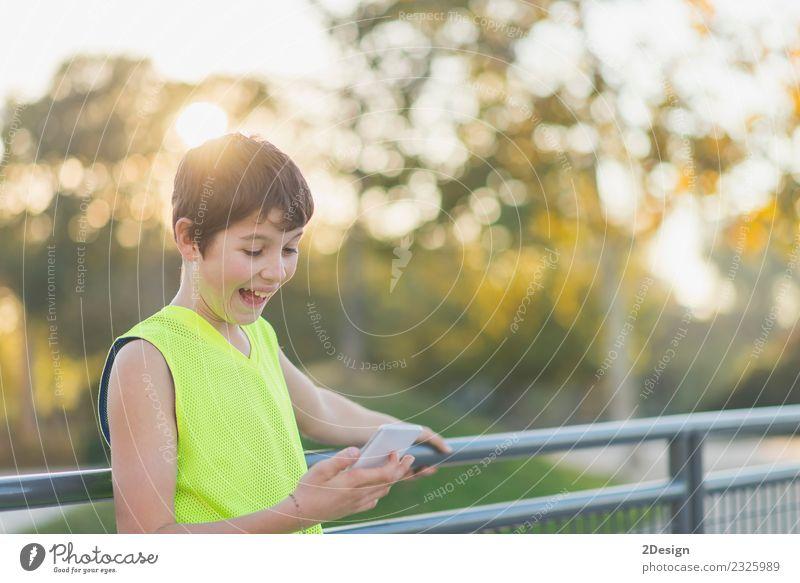 Porträt eines lächelnden Teenagers, der auf seinem Smartphone aussieht. Lifestyle Stil Freude Glück Freizeit & Hobby Dekoration & Verzierung Schule Studium