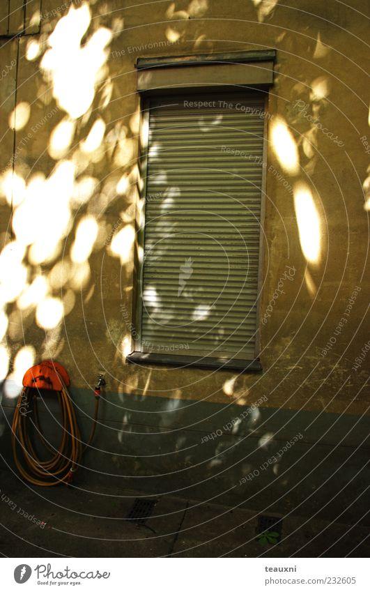 Sonnentaler Haus dunkel Fenster Wand Stimmung Fassade glänzend geschlossen leuchten drehen Surrealismus Wasserhahn Rollo Gartenschlauch