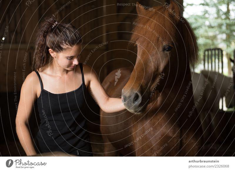 Junge dunkelhaarige lockige Frau mit Pferd im Stall Freizeit & Hobby Reiten Reitsport Reitschule Ferien & Urlaub & Reisen Ausflug Reiterhof Reithalle Mensch