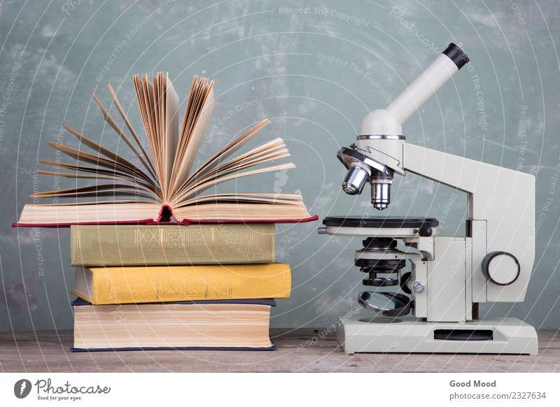 Bücher und Mikroskop auf dem Schreibtisch auf grünem Hintergrund Tisch Wissenschaften Schule lernen Klassenraum Studium Labor Buch Bibliothek schreiben Weisheit