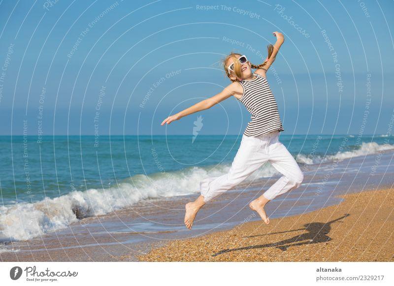 Ein glückliches kleines Mädchen, das tagsüber am Strand spielt. Lifestyle Freude Glück schön Erholung Freizeit & Hobby Spielen Ferien & Urlaub & Reisen Ausflug