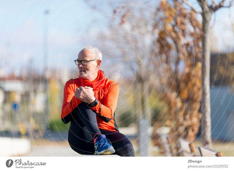 Senior-Läufer, der nach dem Joggen in einem Park sitzt. Lifestyle Glück Gesundheit sportlich Erholung ruhig Freizeit & Hobby Sommer Musik Sport Leichtathletik