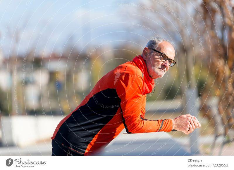 Athletischer Senior-Mann, der sich auf einen Zaun stützt. Lifestyle Körperpflege Gesundheitswesen sportlich Fitness Erholung Freizeit & Hobby Musik Sport