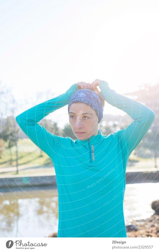 Frau bindet Haare in Pferdeschwanz und macht sich bereit für den Lauf. Lifestyle Stil schön Körper Sport Joggen Erwachsene Baum Park Wald Mode Fitness Erotik