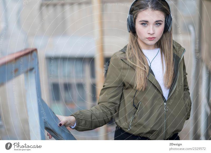 Junge Teenager stehen und Musik hören im Freien Lifestyle Glück Zufriedenheit Haus Schule Headset Fotokamera Technik & Technologie Mensch Frau Erwachsene