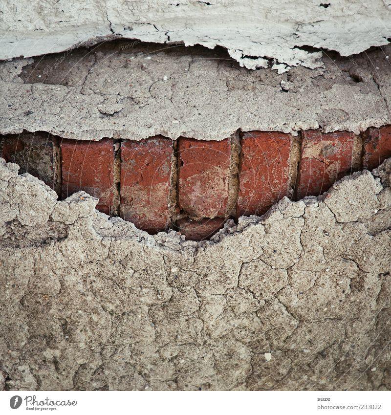 The Joker Mund Zähne Haus Mauer Wand Backstein Lächeln alt eckig einzigartig kaputt trist trocken grau rot Vergangenheit Putz Phantasie Zahn der Zeit Verfall