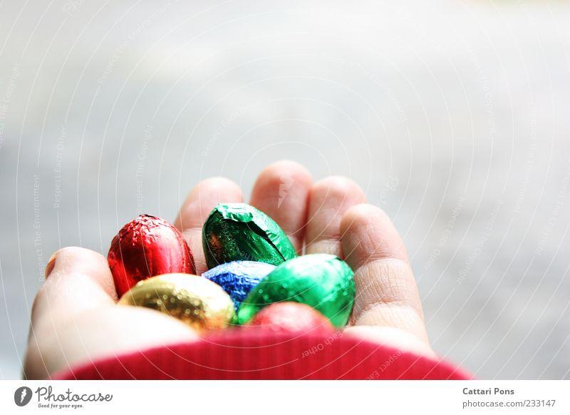 bunte Schokoeier Hand Freude Lebensmittel Glück hell Finger süß festhalten Ostern zart Süßwaren Ei Schokolade zeigen geben Folie