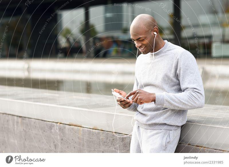 Schwarzer Mann hört Musik mit Kopfhörern im Freien. Lifestyle Glück Sport Telefon PDA Technik & Technologie Mensch maskulin Junger Mann Jugendliche Erwachsene 1