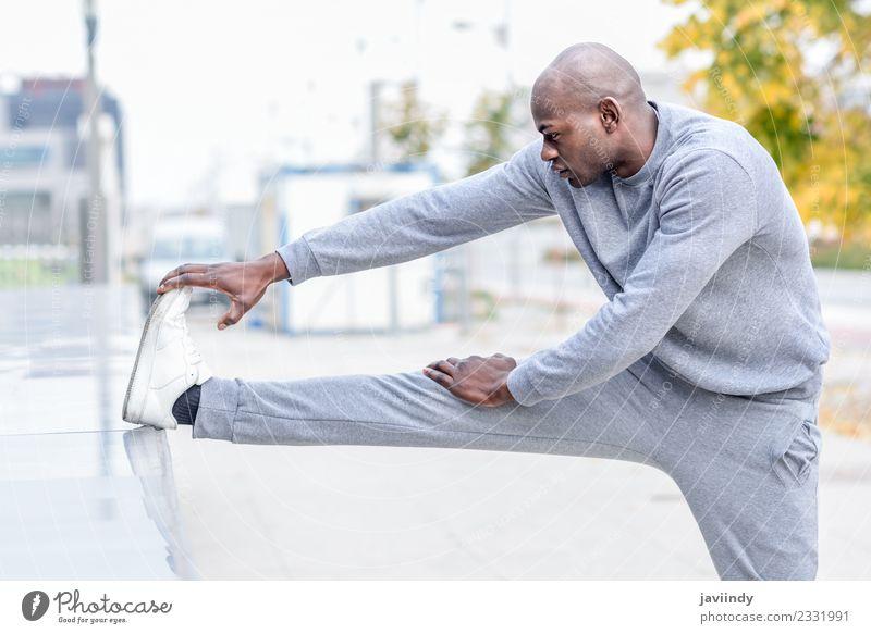 Schwarzer Mann, der sich dehnt, nachdem er im Freien gelaufen ist. Lifestyle Körper Sport Joggen Mensch Erwachsene Jugendliche Beine 1 18-30 Jahre Fitness