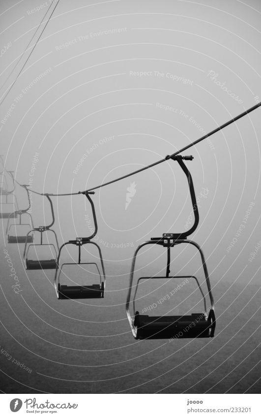 Seilbahn in's Nichts Nebel fahren grau stagnierend Zentralperspektive Nebelbank gruselig Sesselbahn Textfreiraum oben Dunst schlechtes Wetter Schwarzweißfoto